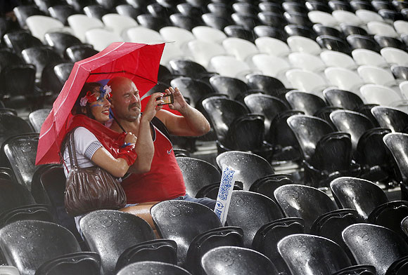 Fans shelter themselves with an umbrella as rain stops play