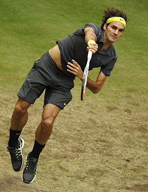 Roger Federer of Switzerland serves the ball to Mikhail Youzhny of Russia
