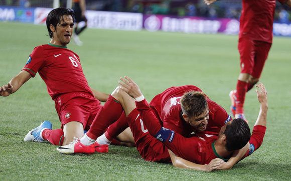 Portugal's players celebrate a goal against Netherlands during their Group B match at Metalist stadium in Kharkiv