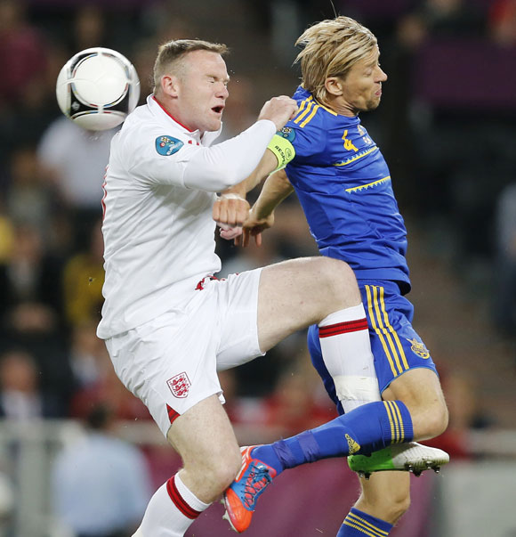 England's Wayne Rooney (L) goes for a header with Ukraine's Anatoliy Tymoshchuk during their Group D match at the Donbass Arena in Donetsk
