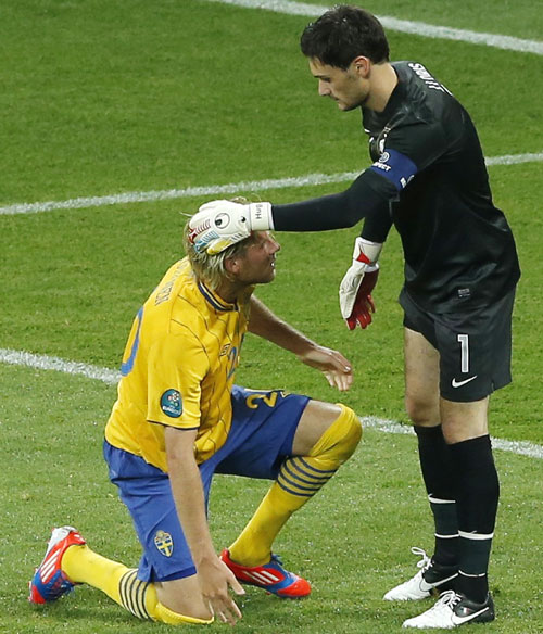 France's goalkeeper Hugo Lloris (R) comforts Sweden's Ola Toivonen after he failed to score a goal during their Group D match at the Olympic stadium in Kiev