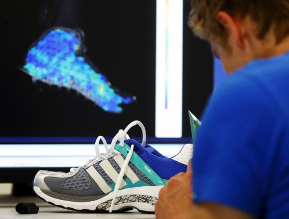 An engineer adjusts test marks on an Adidas running shoe at the Adidas innovation laboratory in Herzogenaurach