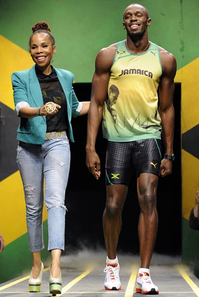 Jamaican sprinter Usain Bolt models the Jamaican team's kit for the London 2012 Olympic Games, designed by Cedella Marley (left)