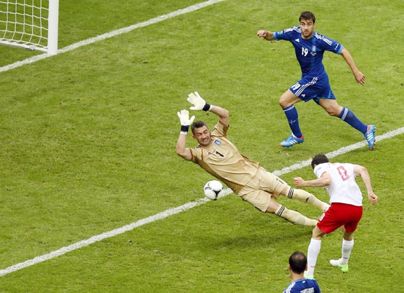 Poland's Robert Lewandowski (No.9) scores the first goal of the tournament past Greece goalkeeper Kostas Chalkias
