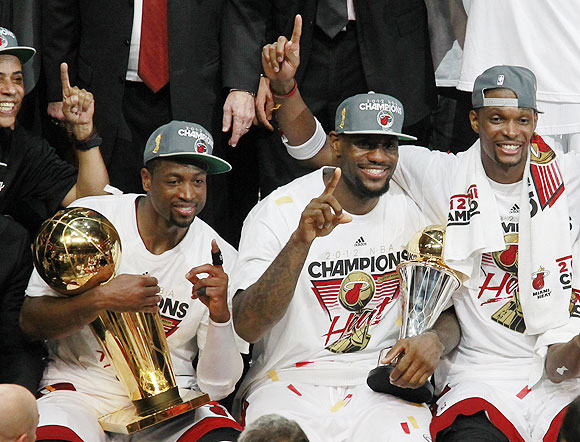 (From left) Miami Heat's Dwyane Wade, LeBron James and Chris Bosh celebrate with the trophy