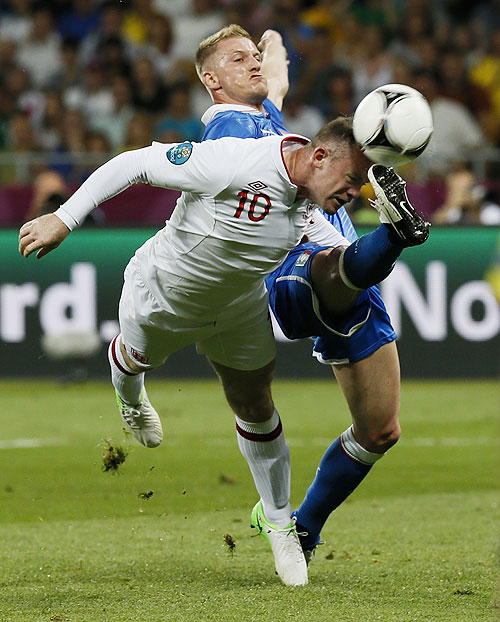 Italy's Ignazio Abate (left) challenges England's Wayne Rooney