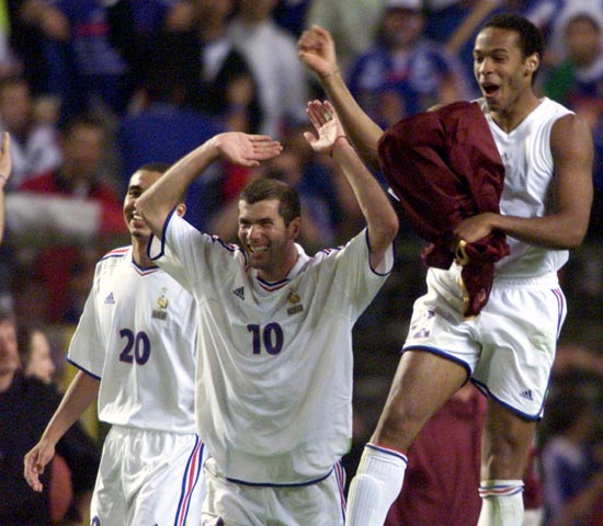 France's Zinedine Zidane (10) celebrates with Thierry Henry (R) and David Trezeguet after winning the match against Portugal