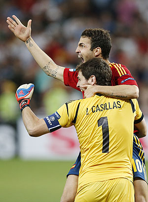 Spain's Cesc Fabregas celebrates with goalkeeper Iker Casillas after scoring the winning penalty goal against Portugal