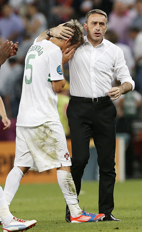 Portugal's Fabio Coentrao (left) is comforted by coach Paulo Bento after losing to Spain