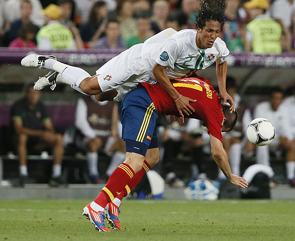 Spain's Alvaro Negredo and Portugal's Bruno Alves (top) fall after an aeriel challenge