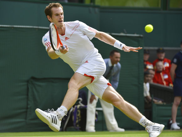 Andy Murray of Britain hits a return to Ivo Karlovic of Croatia during their men's singles tennis match at the Wimbledon tennis championships in London