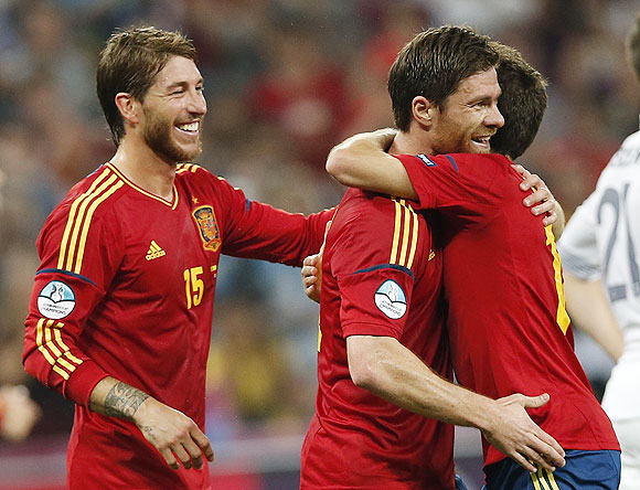 Spain's Xabi Alonso (centre) celebrates with teammates Jordi Alba (right) and Sergio Ramos after scoring against France