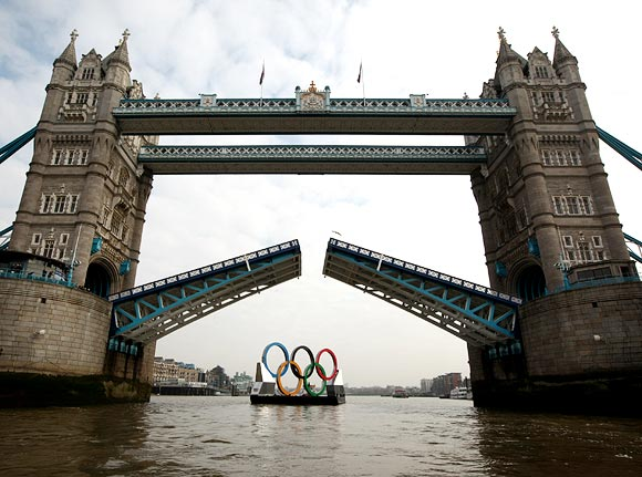 The Tower Bridge opens as the Giant Olympic rings pass through on the river Thames in London
