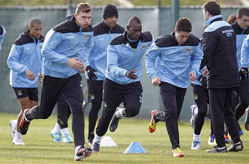 Manchester City players warm up during a practice session
