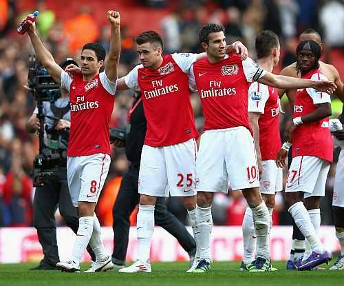 Arsenal players celebrate after winning a match