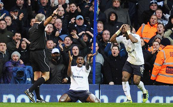 Emmanuel Adebayor (centre) and Louis Saha of Tottenham Hotspur react after referee Martin Atkinson (left) disallowed a goal