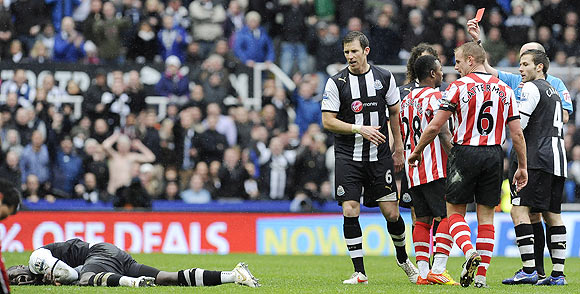 Referee Mike Dean (right) sends off Sunderland's Stephane Sessegnon (3rd from right) for a challenge on Cheick Tiote (left) during their match on Sunday