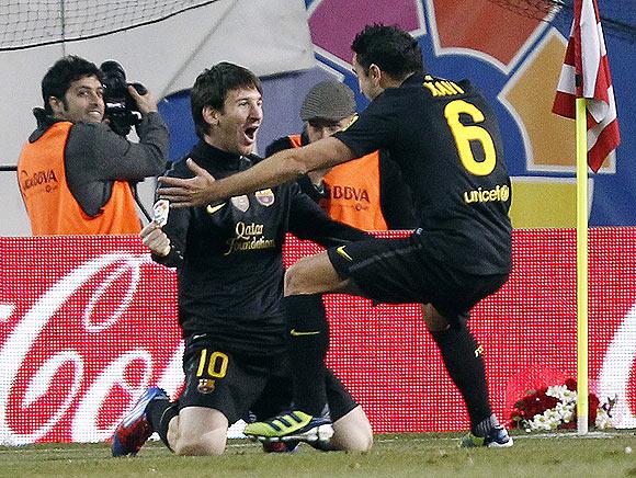 Barcelona's Lionel Messi celebrates with teammate Xavi