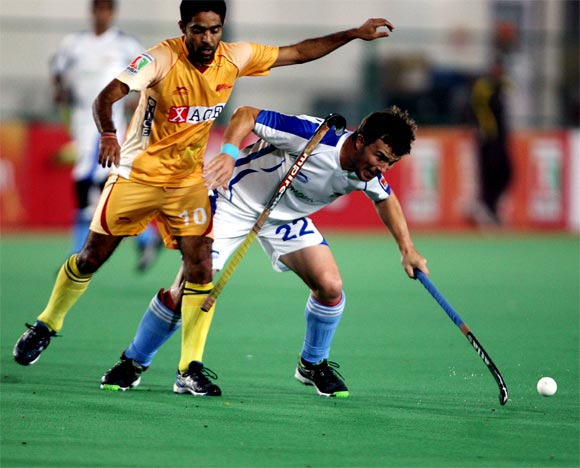 Karnataka's Ravipal Singh loses his stick as he goes for a tackle