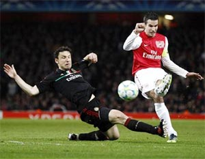 Arsenal striker Robin van Persie (right) is challenged by AC Milan's Mark van Bommel