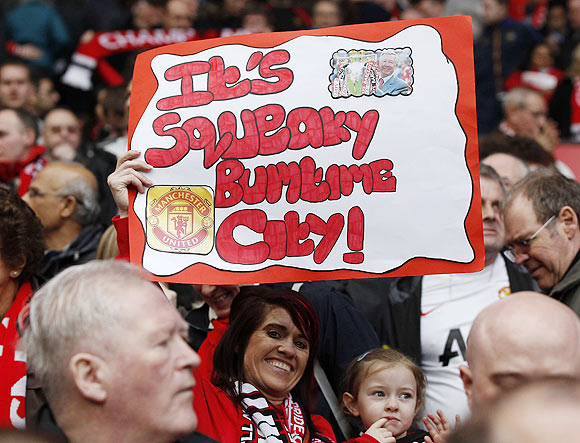 A Manchester United supporter holds a banner during their English Premier League match against West Bromwich Albion at Old Trafford, on Sunday