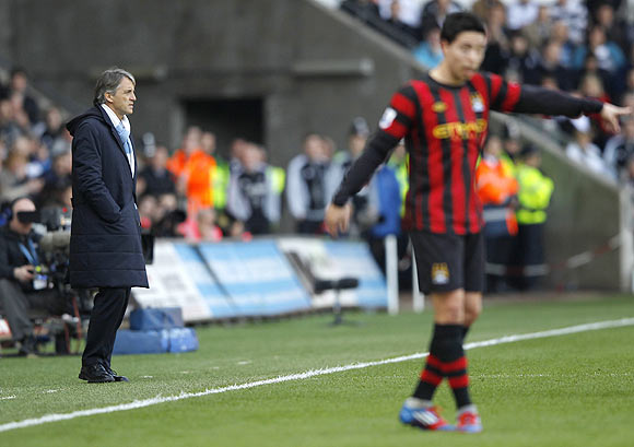 Manchester City manager Roberto Mancini looks on with Sami Nasri in the foreground