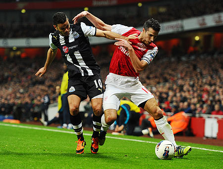 Hatem Ben Arfa of Newcastle and Robin van Persie of Arsenal battle for the ball
