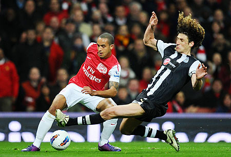 Fabrizio Coloccini of Newcastle tackles Theo Walcott of Arsenal