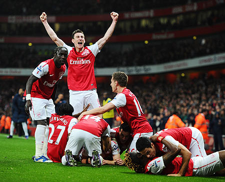 Arsenal players celebrate after Thomas Vermaelen of Arsenal scored their second goal