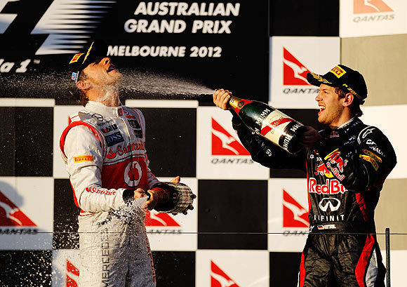 Jenson Button (left) celebrates with second placed Sebastian Vettel on the podium after the Australian GP on Sunday