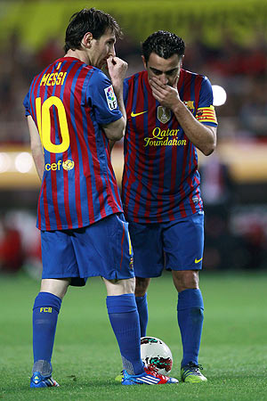 Barcelona's Xavi Hernandez (right) and Lionel Messi prepare to take a free kick