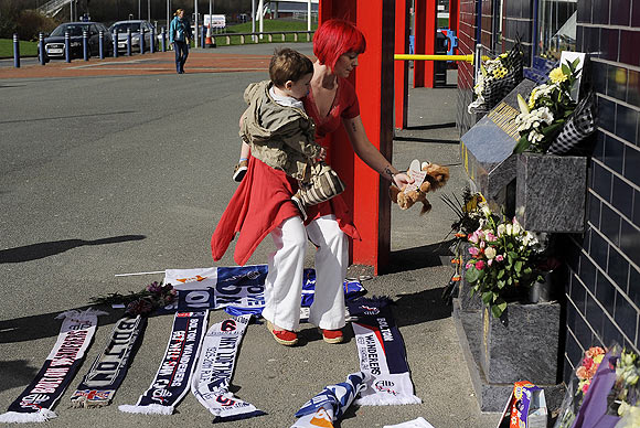 A well-wisher lays a soft toy with a message to Fabrice Muamba at the Reebok stadium in Bolton on Sunday