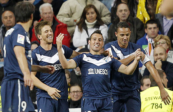 Malaga's Santiago Cazorla (2nd from right) celebrates with teammates after netting against Real Madrid during their La Liga match on Sunday