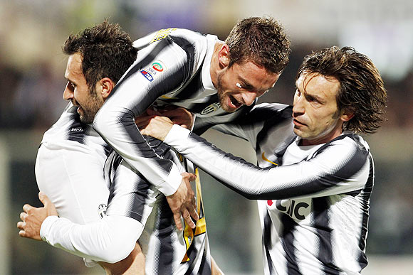 Juventus' Claudio Marchisio (centre) celebrates with teammates Mirko Vucinic (left) and Andrea Pirlo after scoring against Fiorentina during their Serie A match on Saturday