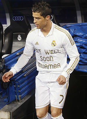 Real Madrid's Cristiano Ronaldo comes out on the field wearing a shirt in support of Muamba before their La Liga match against Malaga on Sunday