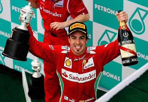 Ferrari's Fernando Alonso celebrates on the podium after winning