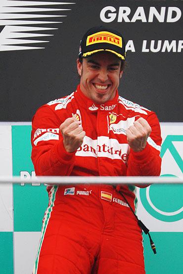 Fernando Alonso celebrates on the podium after winning the Malaysian Formula One Grand Prix on Sunday