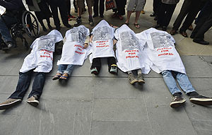 Demonstrators demanding that Dow to be dropped as an Olympics sponsor over the 1984 Bhopal disaster, which killed thousands in India, lie on the pavement outside the venue of an Olympic news conference in central London, on Friday