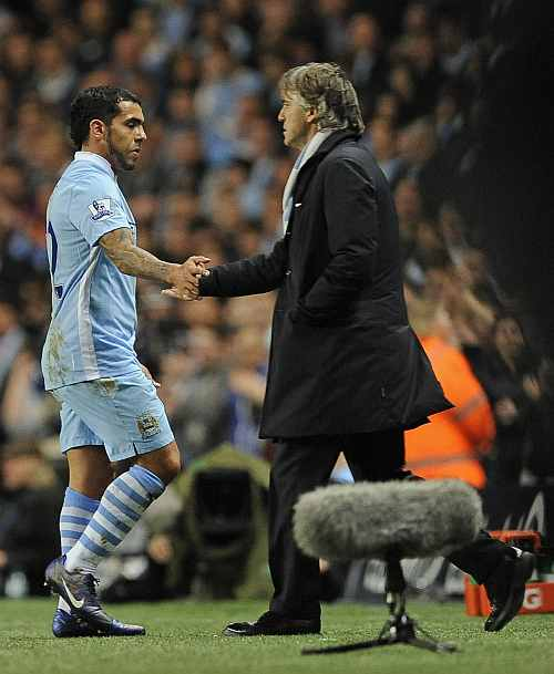 Manchester City's Tevez shakes hands with manager Mancini as he is substituted during their Premier League match at the Etihad stadium