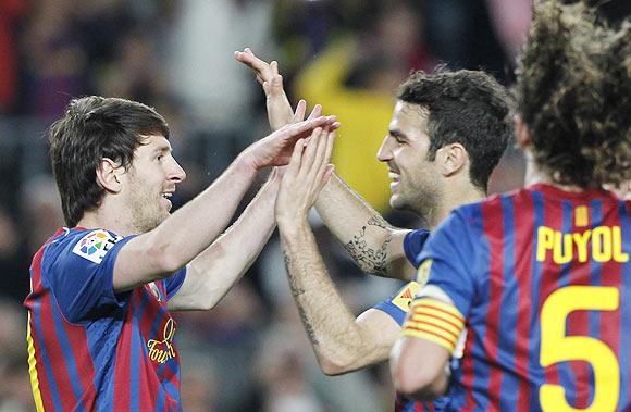 Barcelona's Lionel Messi celebrates with Cesc Fabregas (right) after scoring against Malaga on Wednesday