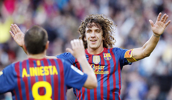 Barcelona's Carles Puyol (right) celebrates with Andres Iniesta after scoring the opener against Malaga on Wednesday