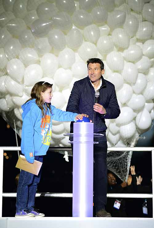 Sebastian Coe and local resident Niamh Clarke-Willis press a button to officially open the Olympic Stadium inside the Olympic Park in London