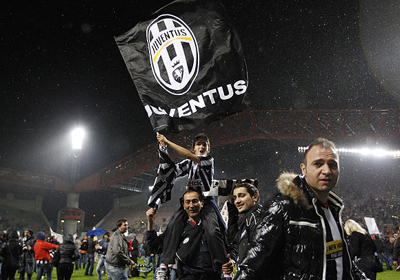 Juventus' fans celebrate after the team won the Serie A title following their match against Cagliari at the Nereo Rocco stadium in Trieste on Sunday