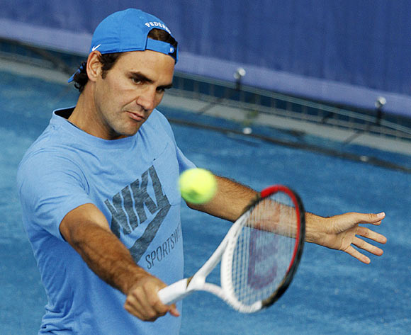 Roger Federer of Switzerland returns the ball during a training session at the Madri