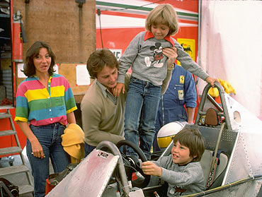 Gilles Villeneuve puts son Jacques at the controls of his Ferrari Formula One racing car whilst being pictured with his family in the Ferrari paddock during the 1979 formula one racing season
