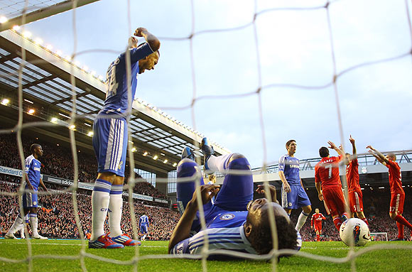 Chelsea's Ryan Bertrand (left) shows his frustration after teammate Michael Essien scores an own goal during their match against Liverpool on Tuesday