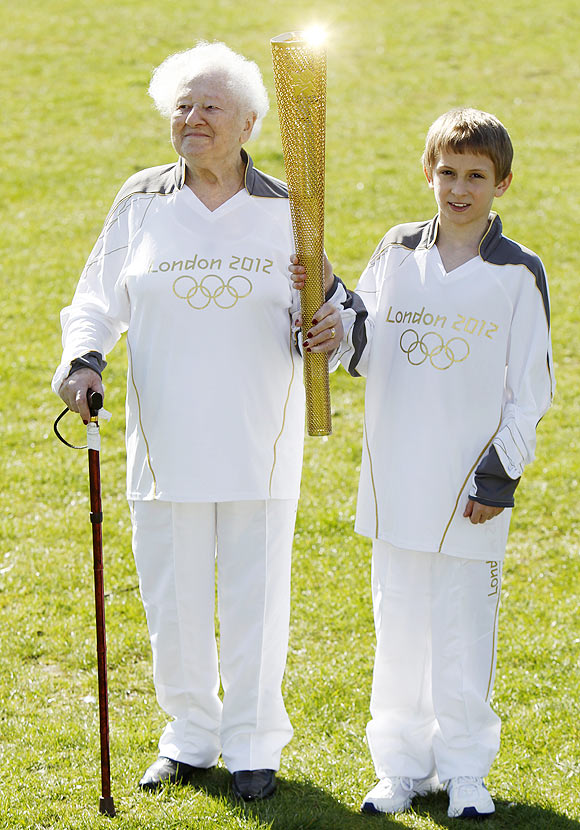 The Oldest Olympic torch bearer for the London 2012 Olympic Games, Dinah Gould (left) who will be 100 when she carries the flame, and the youngest, 11 year old Dominic John MacGowan, pose with an Olympic torch