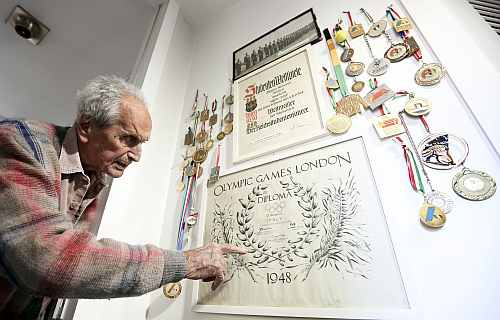 Ottavio Missoni points to the diploma he was given for his participation in the 1948 Olympics in London at his house
