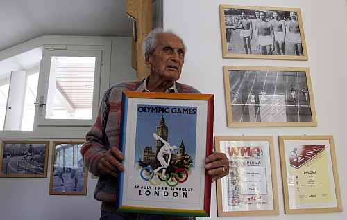 Ottavio Missoni holds a framed poster for the 1948 Olympics in London at his house in Sumirago