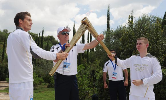 Alex Loukas from Britain lights the London 2012 Olympic Torch from Spyros Gianniotis of Greece during the Lighting Ceremony of the Olympic Flame at Ancient Olympia on May 10, 2012 in Olympia, Greece
